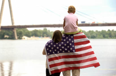 family with american flag looking at bridge over river
